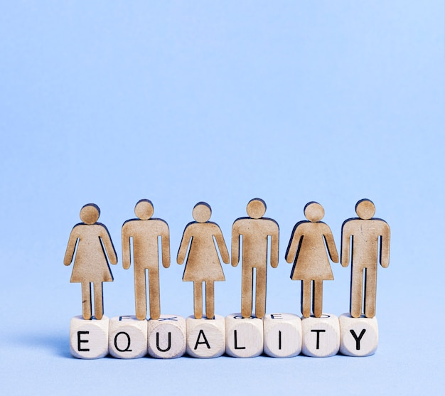 Gente de cartón de pie en la palabra de igualdad escrita en cubos de madera