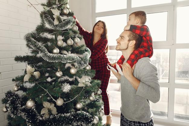 Gente en casa. familia en pijama. madre con esposo e hijo en una decoración navideña.