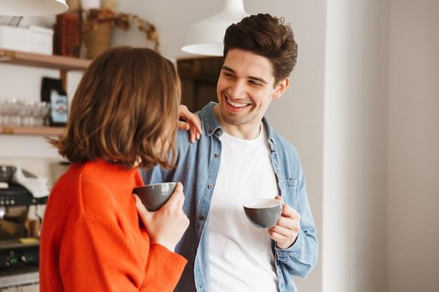 Gente caucásica mujer y hombre en ropa casual sonriendo el uno al otro y tomando café en la cafetería