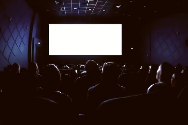Gente en el cine viendo una película. pantalla blanca vacía en blanco