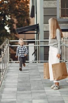 Gente en una ciudad veraniega. madre con hijo. mujer con un suéter gris.