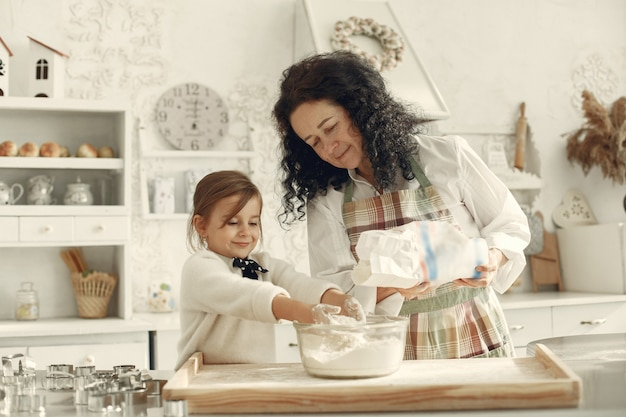 Gente en una cocina. abuela con hija pequeña. mujer adulta enseñar a la niña a cocinar.