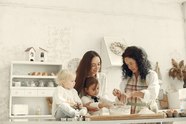 Gente en una cocina. familia prepara pastel. mujer adulta con hija y nietos.
