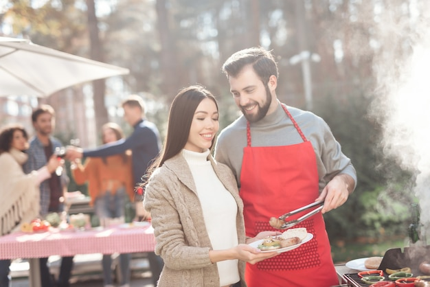 La gente está cocinando comida de barbacoa durante un picnic.