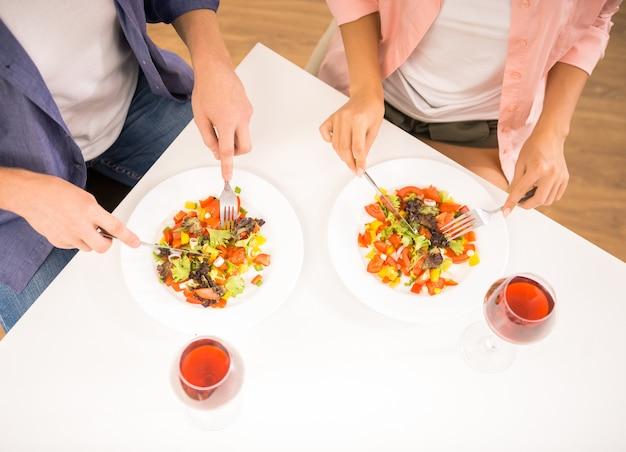 La gente come ensalada en la cocina.