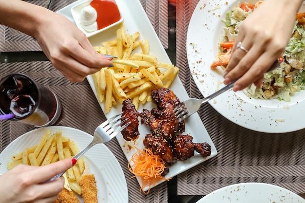 Gente comiendo alitas de pollo con salsa barbacoa y papas fritas