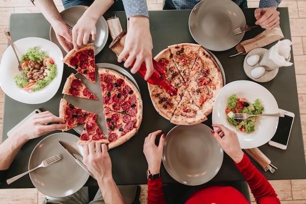 Gente comiendo pizza en un restaurante