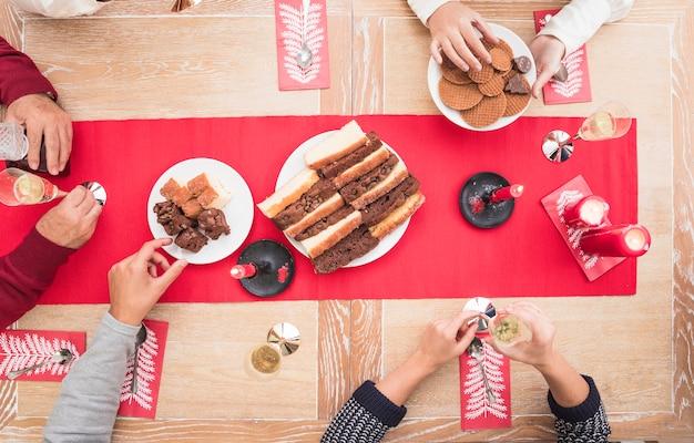 Gente comiendo postre en mesa navideña