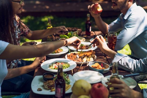 La gente está comiendo en vacaciones. ellos comen fuera de la casa.