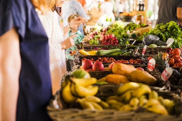 Gente comprando vegetales en un puesto en el mercado.
