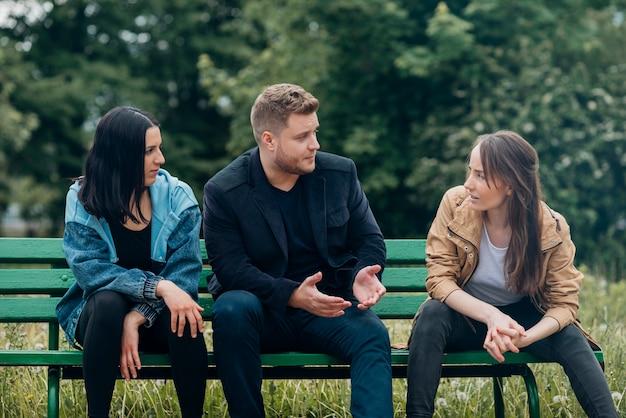 Gente conflictiva sentada en un banco y hablando