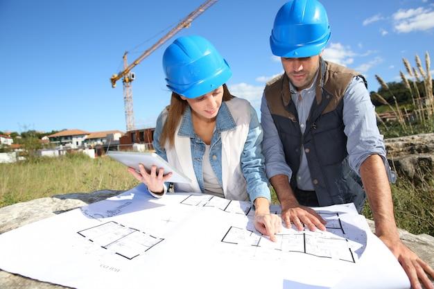 Gente de construcción mirando plano