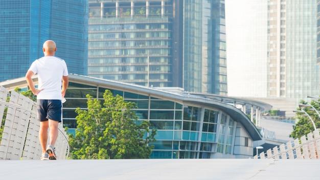 La gente corre en el puente peatonal de la ciudad con el edificio moderno exterior