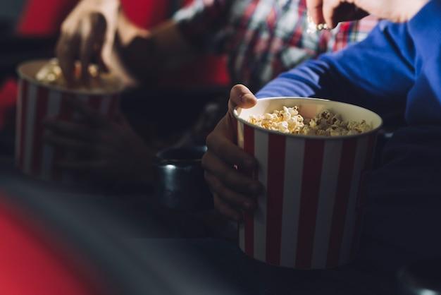 Gente de cultivos comiendo palomitas de maíz en el cine