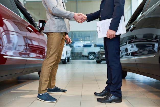 Gente dándose la mano en la sala de exposición de automóviles