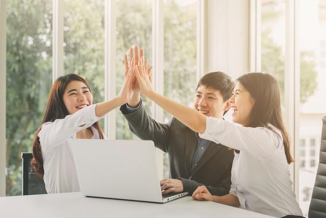 Gente de negocios dando cinco altos para celebrar el éxito