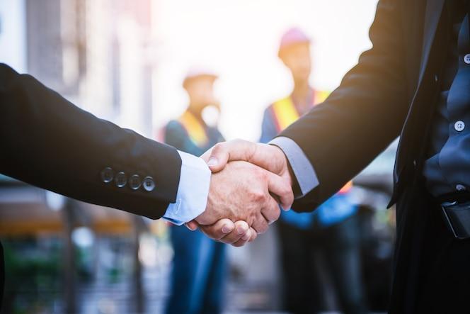 Gente de negocios dándose la mano con fondo de ingeniería.