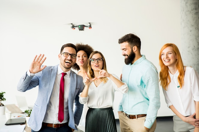 Gente de negocios dejando que la cámara de drones vuele sobre la oficina y se divierta