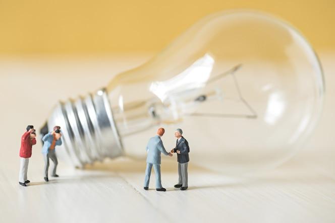 Gente de negocios en miniatura hace un acuerdo de apretón de manos con el fondo de la bombilla