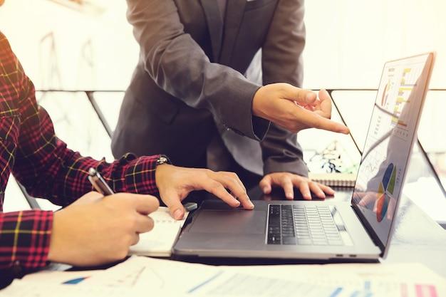 Gente de negocios hablando de plan de negocios y apuntando a la pantalla del portátil para explicar