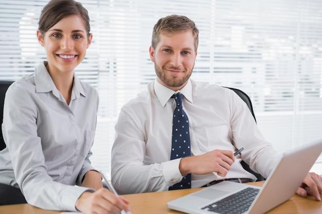 Gente de negocios sonriendo a la cámara con la computadora portátil