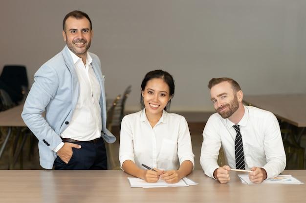 Gente de negocios sonriente posando en el escritorio en la oficina