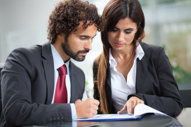 Gente de negocios trabajando en un documento mientras está sentado en una cafetería