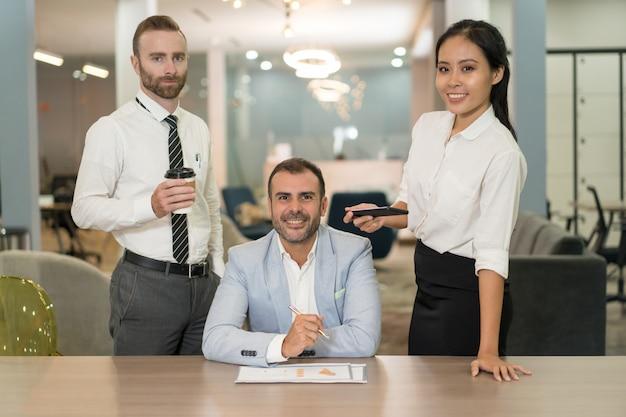 Gente de negocios trabajando y posando en el escritorio en la oficina