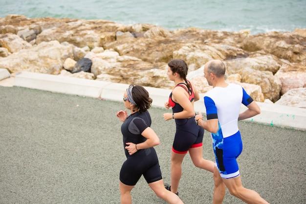 Gente deportiva corriendo en la costa del mar