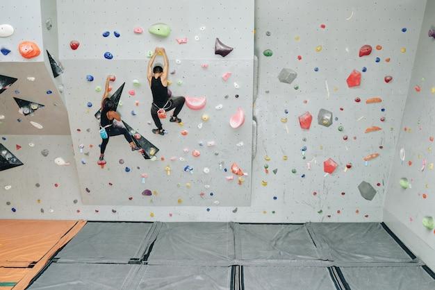 Gente deportiva trabajando en muro de escalada