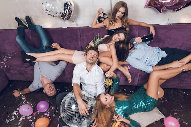 La gente descansa después de una fiesta tumultuosa en un club nocturno.