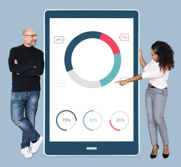 Gente diversa alegre que muestra un gráfico circular en una tableta