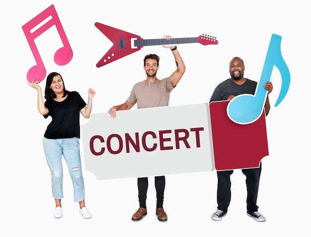 Gente diversa alegre sosteniendo iconos de música