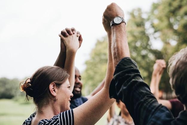 Gente diversa feliz tomados de la mano en el parque