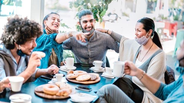 Gente divirtiéndose bebiendo y comiendo en la cafetería.