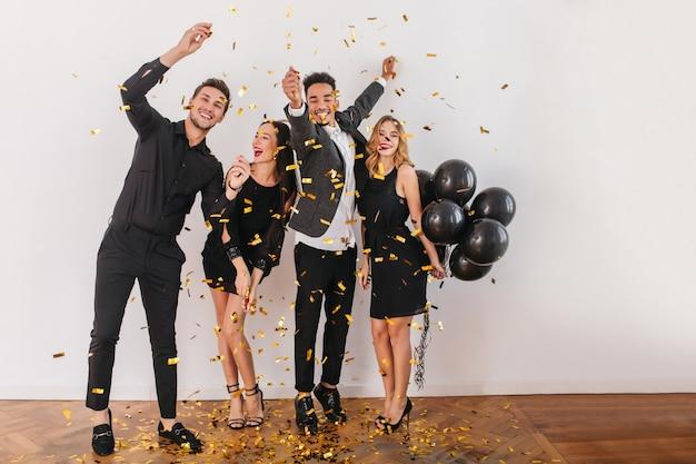 Gente divirtiéndose en la fiesta con globos negros y confeti.