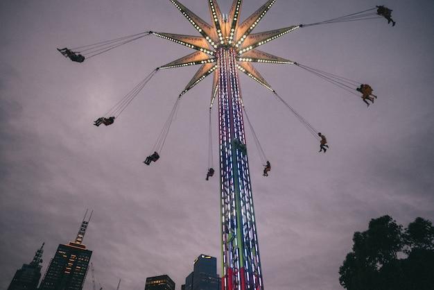 Gente divirtiéndose en grandes columpios altos y coloridos