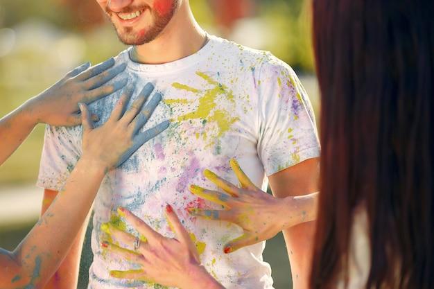 Gente divirtiéndose en un parque con pinturas holi