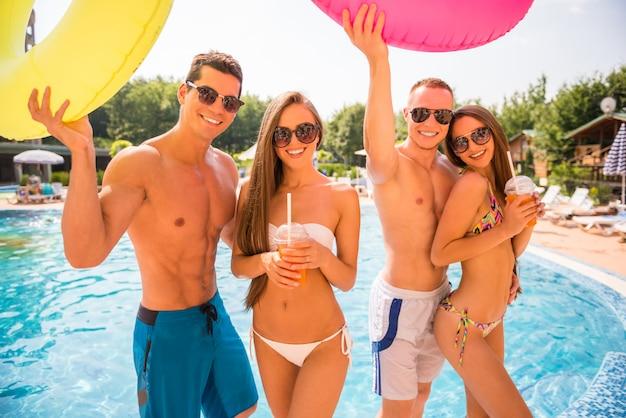Gente divirtiéndose en la piscina con anillos de goma de colores.