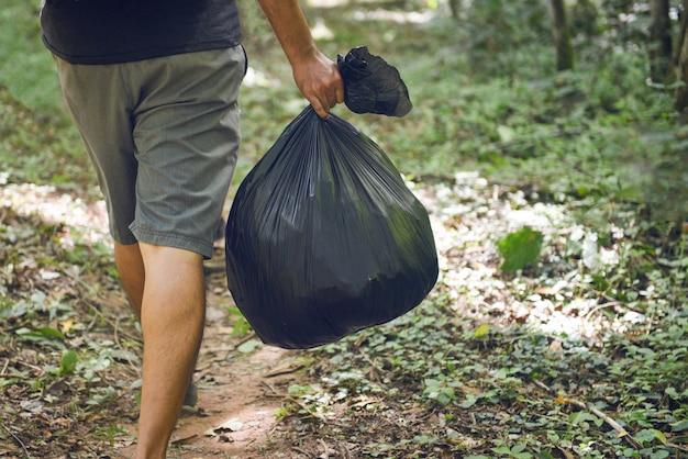 Gente de la ecología de la recolección de basura que limpia el parque, mano del hombre que sostiene bolsos de basura plásticos negros