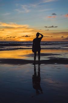 Gente en la playa al atardecer. la niña está saltando contra el telón de fondo del sol poniente.