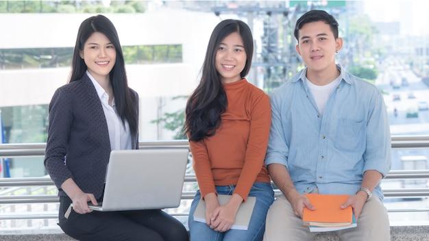 La gente enérgica optimista de los adolescentes y la mujer de negocios se sientan y sonríen en banco