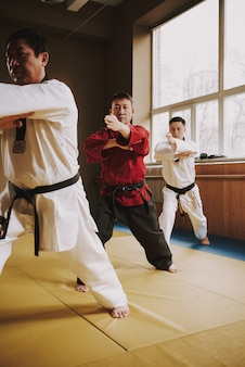 La gente entrena ataques en la sala de combate en karate.