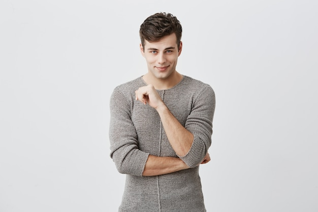 Gente, estilo, concepto de moda. apuesto joven europeo con elegante corte de pelo y ojos azules, vistiendo un suéter posando en el interior, manteniendo los brazos cruzados, mirando con una hermosa sonrisa coqueta