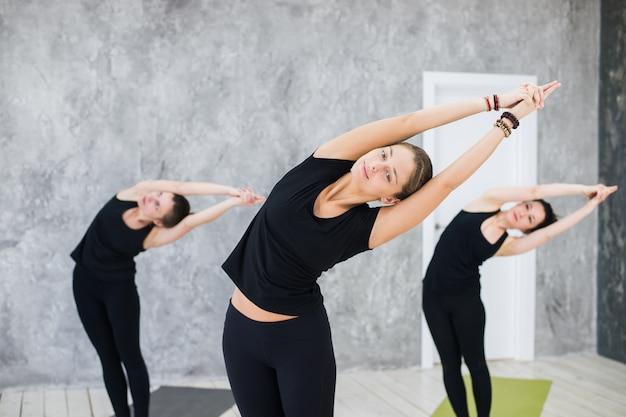 Gente estirándose y sonriendo en clase de yoga