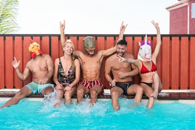 Gente feliz bailando en la fiesta privada de la piscina mientras usa divertidas máscaras de animales