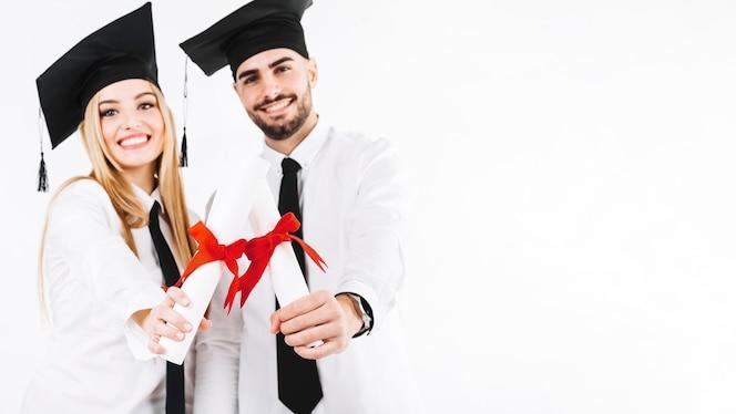 Gente feliz de pie con diplomas