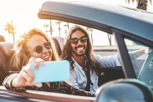 Gente feliz divirtiéndose en un auto convertible haciendo videos para redes sociales - pareja joven disfrutando de vacaciones en descapotable al aire libre - viajes, estilo de vida juvenil y concepto de pasión por los viajes - centrarse en la cara del hombre