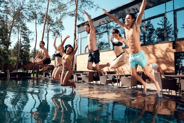 Gente feliz divirtiéndose saltando de la piscina al agua.