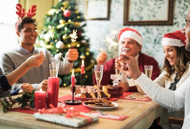 Gente feliz con fuegos de bengala encendidos en mesa festiva